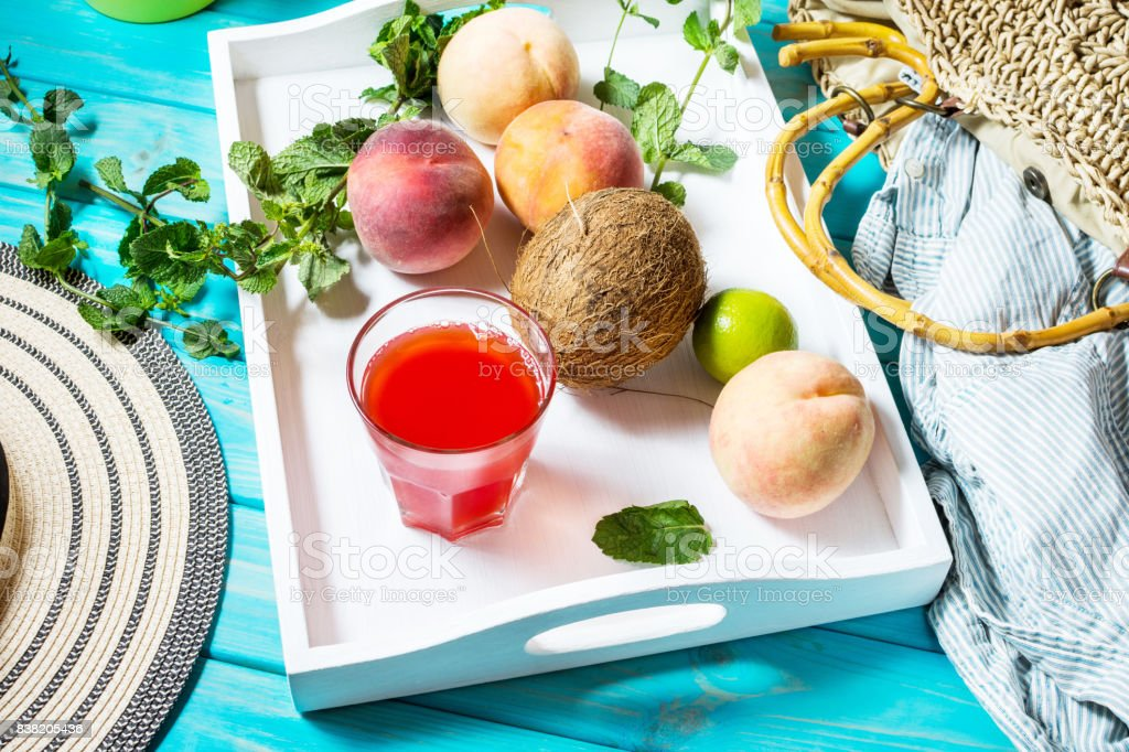 Summer vacation background theme with bag, hat, coconut, sunglasses and Peaches on blue wood background. stock photo
