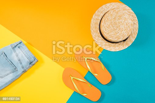 istock Summer vacation background with orange flip flops, denim trousers and hat on colored copy space 691493134