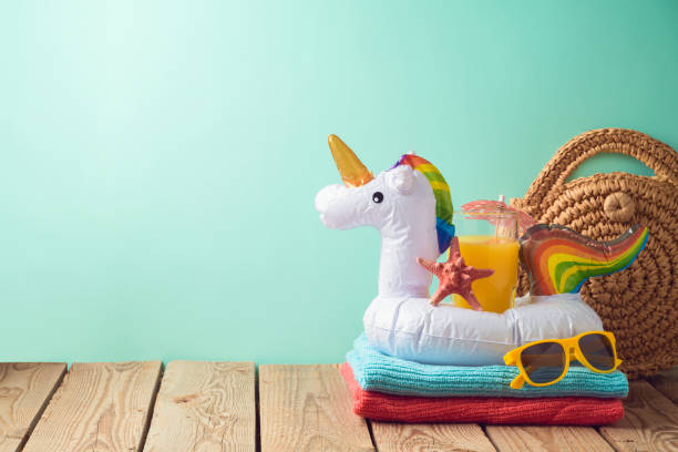 Summer vacation background with orange juice and unicorn pool float on wooden table stock photo