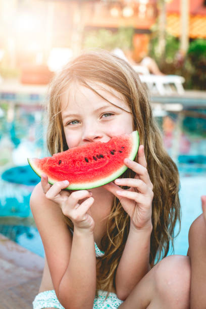 Sommerferien - Kinder essen Wassermelone am Pool in thailand – Foto