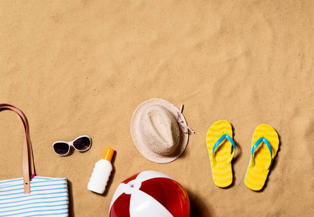 summer vacation composition. flip flops, hat and other stuff - beach ball stock photos and pictures