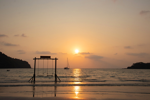 Summer vacation concept. Beautiful silhouette empty wood swing sunset or sunrise on the beach in Phuket, Thailand.