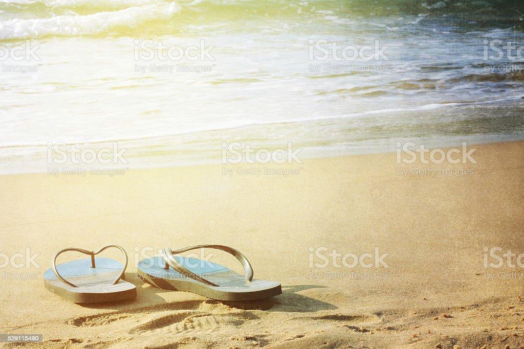 Summer vacation concept. Flip flops on a sandy ocean beach stock photo
