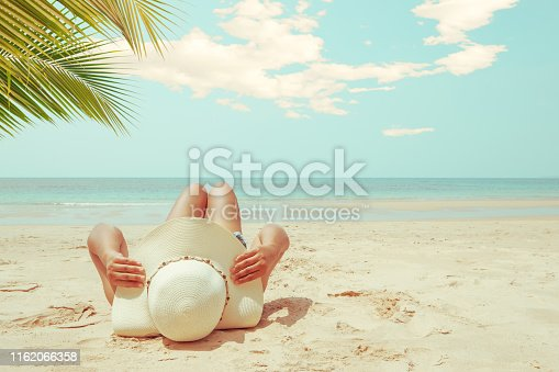 Leisure in summer - Young woman in straw hat lying sunbathe on a tropical beach. Memories of summer vacation concept. retro color tone.