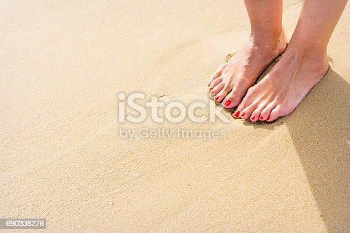 Female feet with red nail polish on yellow sandy beach. Shot taken on beautiful beach near Syracuse, Italy