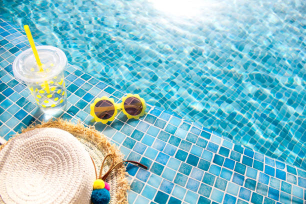 Summer vacation concept. Stylish yellow sunglasses, hat and fresh cocktail. Summer vacation concept. Stylish yellow sunglasses, hat and fresh cocktail. Flat lay. Space for text. Time to travel swimming pool stock pictures, royalty-free photos & images