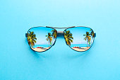 Summer vacation concept. Sunglasses with ocean beach and palms on blue background