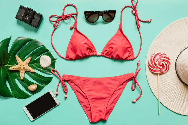 Summer vacation concept with pink bikini suit, hat and accessories Red, pink bikini suit, lollipop, sunglasses, smartphone, film camera, hat on plain light cyan background. Empty space for copy, text, lettering. Summer vacation concept. bikini stock pictures, royalty-free photos & images