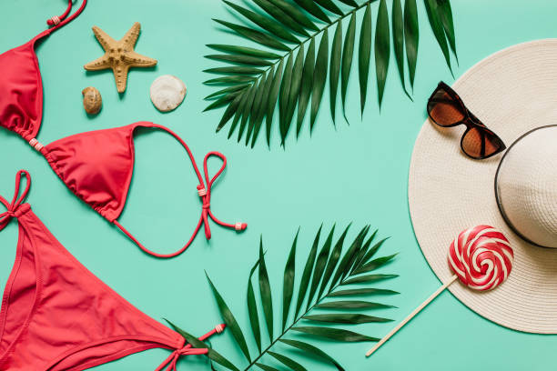 Summer vacation concept with pink bikini suit, hat and accessories Red, pink bikini suit, lollipop, sunglasses, sea star on plain light cyan background. Empty space for copy, text, lettering. Summer vacation concept. swimwear stock pictures, royalty-free photos & images