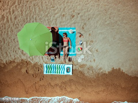 Aerial view photo of a young couple sunbathing on the beach, and using some of the beach essentials: parasol, floating devices, scuba-mask..