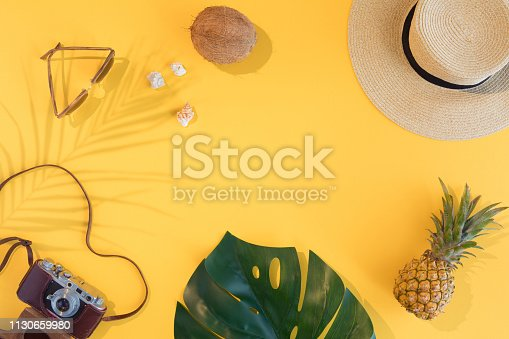Summer vacation flat lay concept on yellow background. Tropical accessories top view. Space for text.