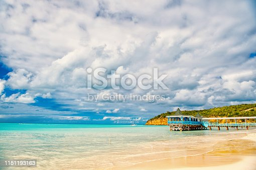 istock Summer vacation on caribbean. Sea beach with wooden shelter in antigua. Pier in turquoise water on cloudy sky background. Wanderlust, travel, trip. Adventure, discovery, journey 1151193163