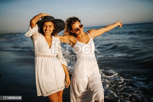Young female friends in white dresses enjoying summer day on the beach