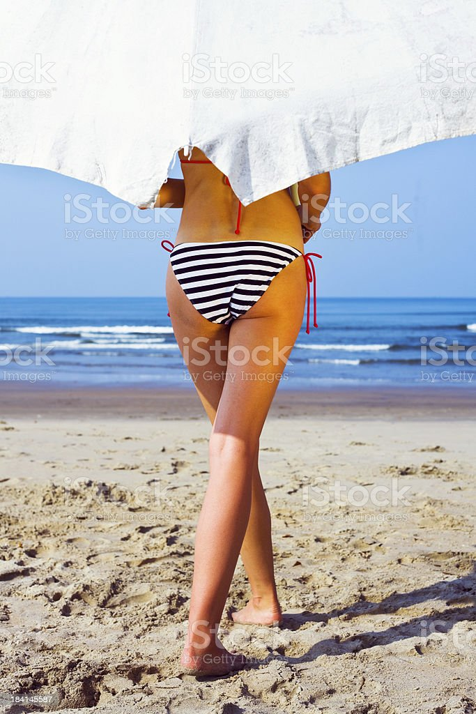 Summer vacation Sexy woman wearing striped bikini walking on a beach with white umbrella. Back view. Adult Stock Photo