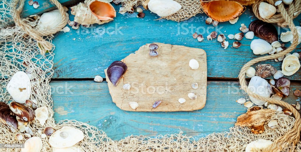 Summer vacation relaxation background theme with seashells, fishing net, rope, stones and weathered wood blue background with copy space. Vintage toning. Wide photo stock photo