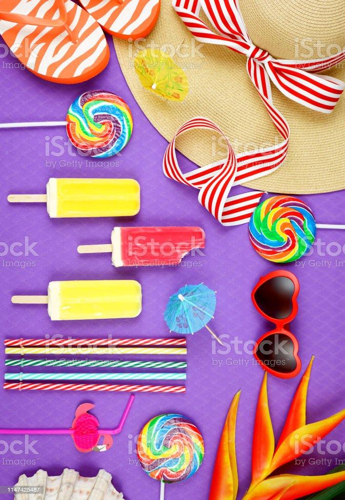 Summer vacation theme flatlay overhead with sunhat, lollipops, ice...