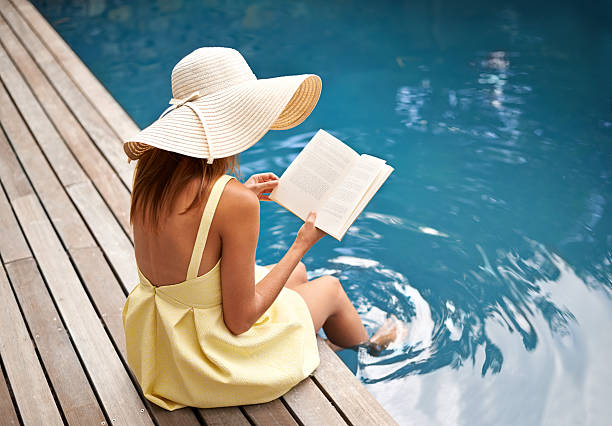 Summer vacation with a great book Rearview shot of a woman relaxing by the pool with a book poolside stock pictures, royalty-free photos & images