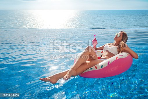 istock Summer Vacation. Woman in bikini on the inflatable mattress in the SPA swimming pool. 802390626