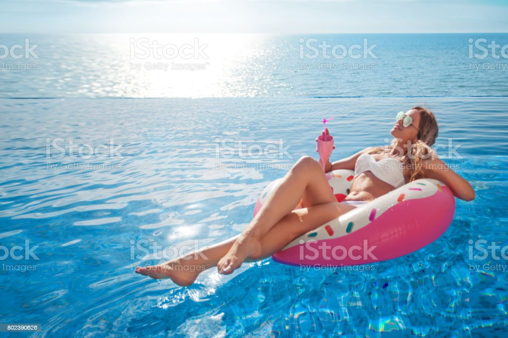 Summer Vacation. Woman in bikini on the inflatable mattress in the SPA swimming pool. stock photo