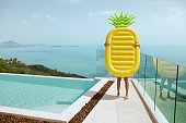 Summer vacation. Woman with pineapple float having fun near infinity swimming pool with sea on background. Person with pool toy at luxury resort