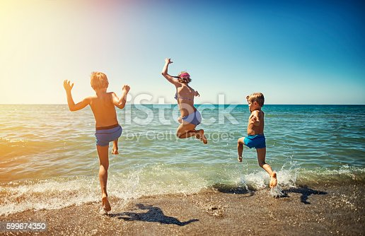 istock Summer vacations in Italy - kids jumping into the sea 599674350