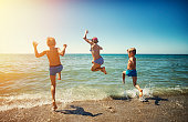 Three kids - a girl and two boys  - are having fun in sea.  Kids are jumping in the sea. Sunny summer day in Tuscany, Italy. Beautiful sandy beach in Tirrenia.
