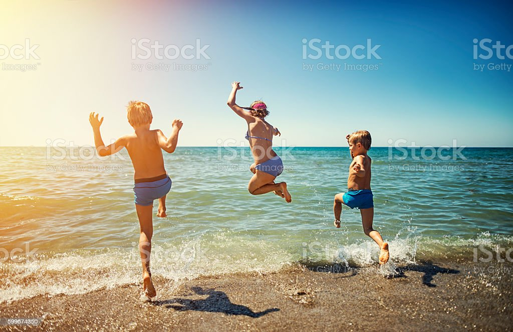 Summer vacations in Italy - kids jumping into the sea - fotografia de stock