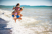Three kids - a girl and two boys  - are having fun in sea.  Kids are jumping over a wave into the sea. They are caught mid air flying into the sea fun.