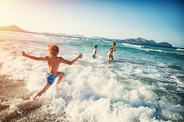 summer vacations - kids playing at sea - jumping into water stock pictures, royalty-free photos & images