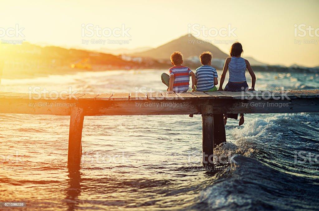 Summer vacations - kids sitting on sea pier stock photo
