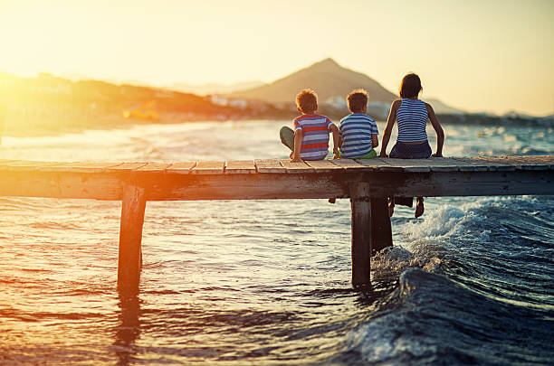 Summer vacations - kids sitting on sea pier stock photo