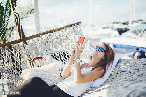 Relaxed woman in hammock using smartphone
