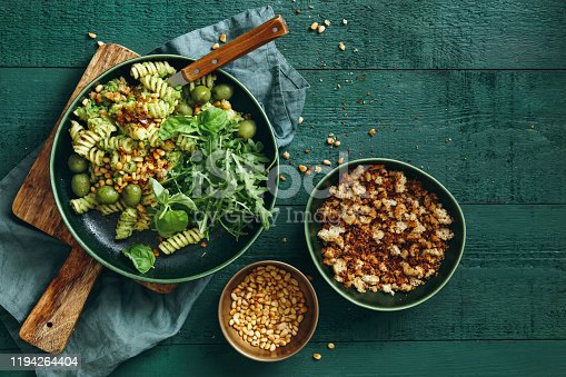 Summer vegetarian pasta salad with broccoli pesto, peas, arugula, olives, pine nuts and bread crumbs on dark green background. Top view.