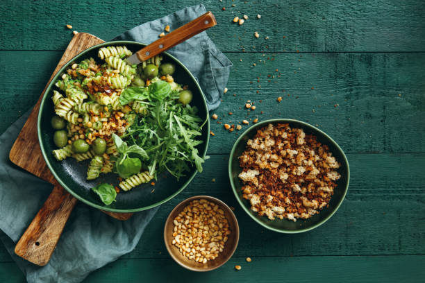 Summer vegetarian pasta salad with broccoli pesto Summer vegetarian pasta salad with broccoli pesto, peas, arugula, olives, pine nuts and bread crumbs on dark green background. Top view. vegetarian stock pictures, royalty-free photos & images