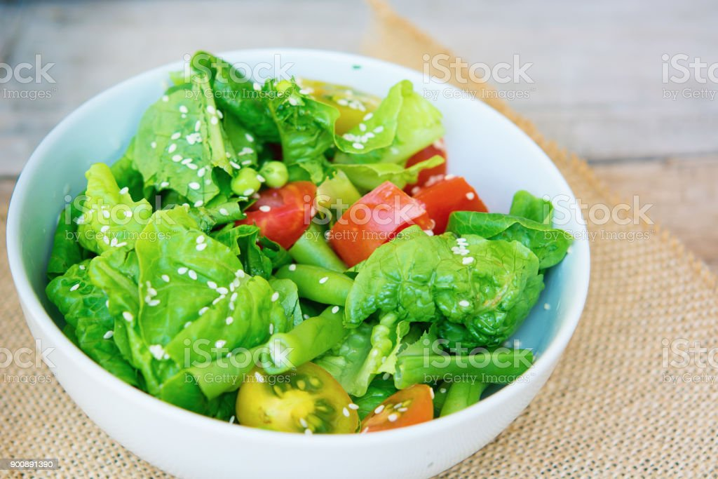Summer vegeterian salad with tomatoes, green pea, green beans, sesame and bell paper in the bowl on the rustic table. Organic food, detox. stock photo