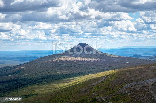 Beautiful summer view from one of the peaks,  over the Swedish mountains or fjeld word in Northern Sweden with sunshine,  blue sky and fluffy white clouds