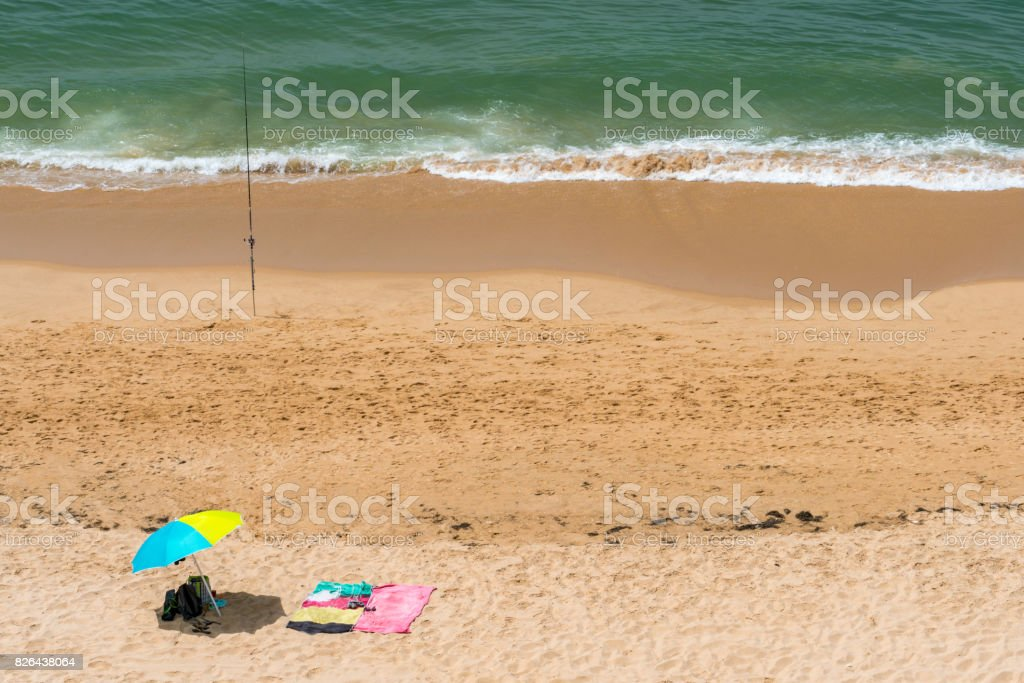 Summer view from above of sun parasols and a fishing rod on a sunny beach. stock photo