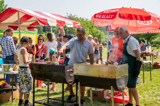 Summer view of two males barbecue grilling outdoors on a green lawn in a park with people and parasols on the Swedish national day. stock photo