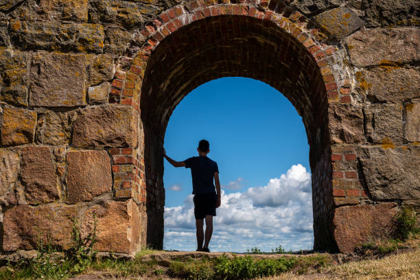 Summer view, silhouette of a young boy man leaning against an ancient old stone wall inside an arched gate looking at the blue sky. Varberg Fortress in Sweden. stock photo
