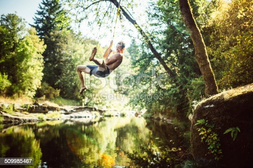 A man swings out over a pristine river on a rope swing, a smile on his face as he enjoys the fun.  Horizontal image with copy space.