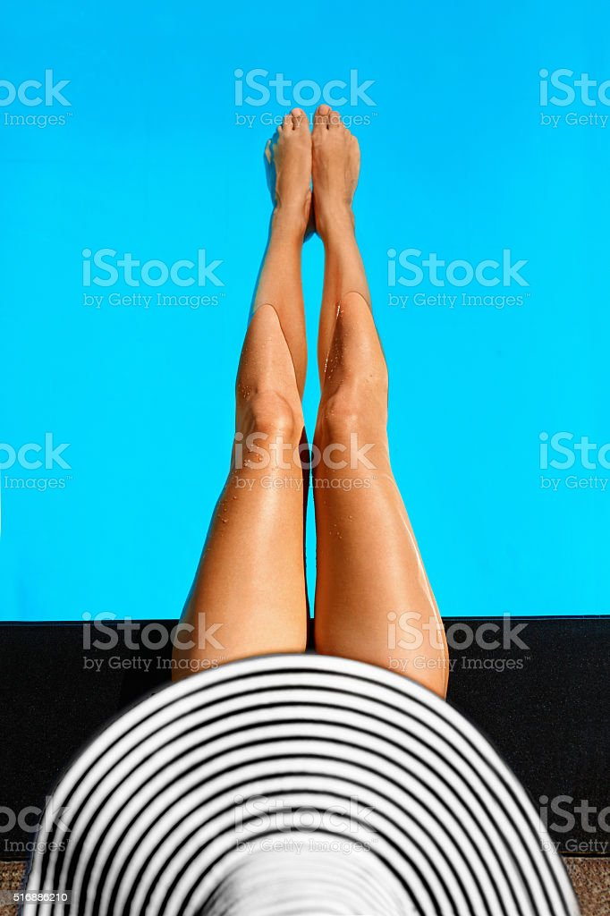 Summer Woman Body Care. Long Female Legs In Swimming Pool stock photo