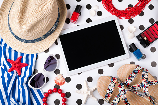 Summer women's accessories: sunglasses, hat, jewelry, cosmetics, sandals, shirt and tablet on creative background. Vacations, travel and freelance work concept. Top view