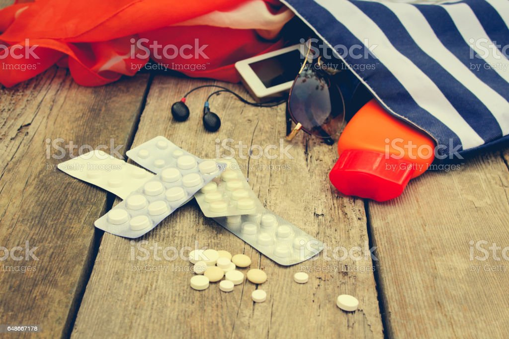 Summer women's beach accessories for your sea holiday and pill on old wooden background. Concept of medication required in journey. bildbanksfoto