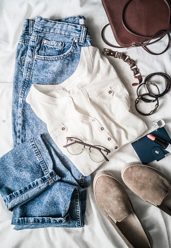 640200626 istock photo Summer women's fashion clothes set - mom's jeans, suede sneakers, cotton t-shirt, leather bag, bracelets, lipstick on a light background, top view. Beauty, fashion concept. Flat lay 1130980020