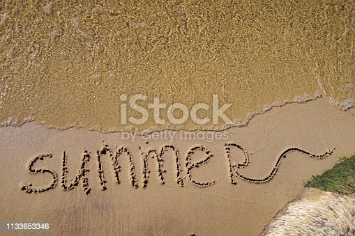 istock Summer written on the sea sand. Natural sandy background with beach and transparent pure wave. Place for text 1133653346