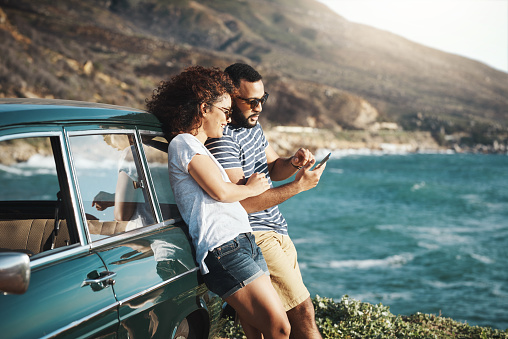Shot of a young couple using a mobile phone on a road trip