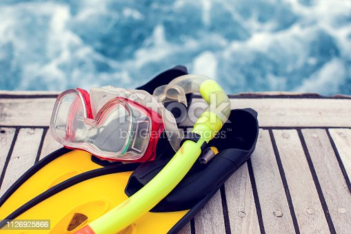 Summertime concept. Sea view. Diving mask and flippers lelft on boat.