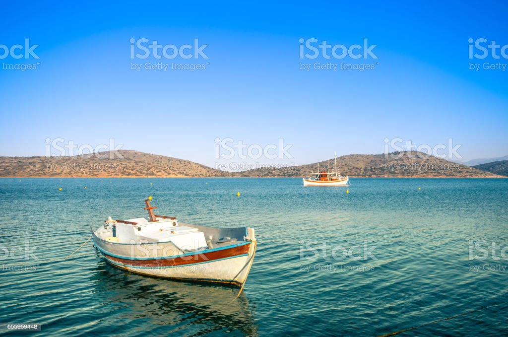 Summertime Background. Traditional wooden fishing boat at Elounda, Crete, Greece. stock photo