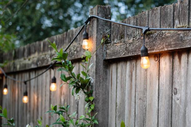 zomer achtertuin hek met verlichting - snoerverlichting stockfoto's en -beelden