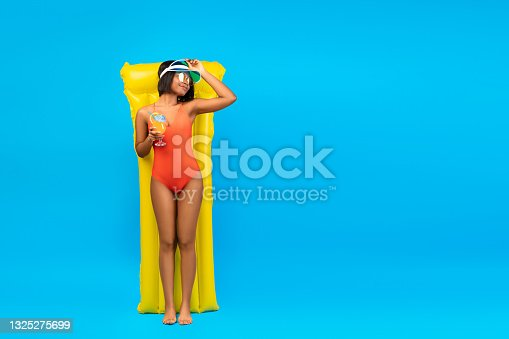 istock Summertime chillout. Sensual young black lady in bikini enjoying fresh cocktail while lying on inflatable lilo 1325275699